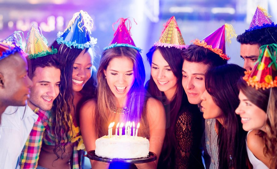 Group of people in a birthday party about to blow the candle