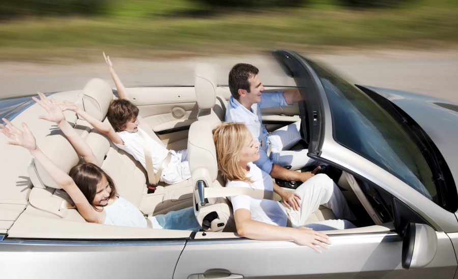 Portrait of a happy family with open arms in a new convertible car.  Side view.