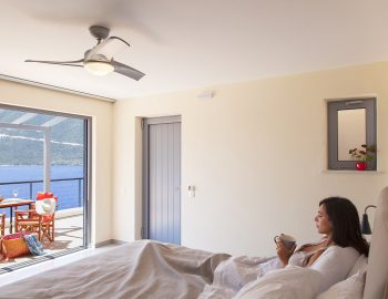 vasiliki-boutique-suites-girl-in-bed-drinking-coffee-looking-at-sea-view