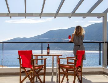 vasiliki-boutique-suites-lefkada-girl-on-balcony-with-wine
