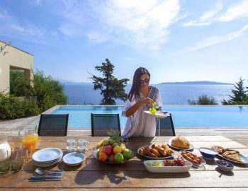 villa-aurora-lefkada-lefkas-afteli-outdoor-breakfast-table-girl-sea-view
