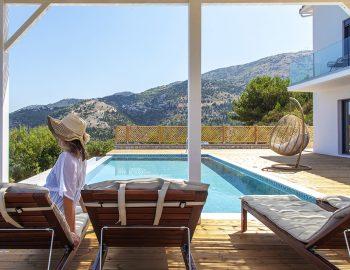 villa-sunset-kalamitsi-lefkada-greece-girl-sitting-on-sunbed-under-pergola